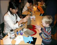 A Next Generation middle school student (left) shows a young science museum visitor the